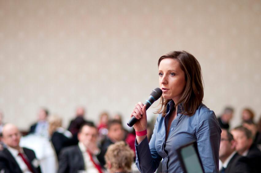Vrouw presenteert met microfoon in haar hand