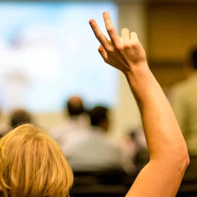 Vrouw steekt haar hand op